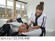 Купить «Young women in hair salon washing customer's hair», фото № 33318448, снято 4 апреля 2020 г. (c) PantherMedia / Фотобанк Лори
