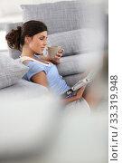 Купить «Brunette woman reading magazine at home in nightwear», фото № 33319948, снято 14 июля 2020 г. (c) PantherMedia / Фотобанк Лори