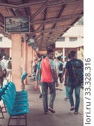 People locals and tourists go on 1 track of the railway station platform in Galle Sri Lanka (2019 год). Редакционное фото, фотограф katalinks / Фотобанк Лори
