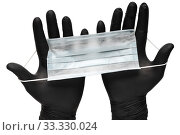 Medical man holds antivirus face mask in hands in black medical gloves. Isolated on white background. Стоковое фото, фотограф А. А. Пирагис / Фотобанк Лори