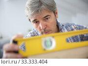 Купить «Closeup of craftsman using level», фото № 33333404, снято 6 июня 2020 г. (c) PantherMedia / Фотобанк Лори