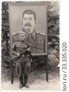 Купить «Советский солдат с пулеметом ППШ на фоне плаката Сталина. Старая фотография времён СССР 1950-х годов», иллюстрация № 33335020 (c) александр афанасьев / Фотобанк Лори