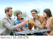 Купить «Group of friends cheering at restaurant terrace», фото № 33335676, снято 12 июля 2020 г. (c) PantherMedia / Фотобанк Лори