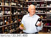 Купить «Serious retiree chooses white and red wine in a liquor store», фото № 33341400, снято 5 апреля 2020 г. (c) Яков Филимонов / Фотобанк Лори