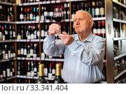 Купить «Older man inspecting quality of red wine in wine store in search of perfect wine for solemn occasion», фото № 33341404, снято 11 июля 2020 г. (c) Яков Филимонов / Фотобанк Лори