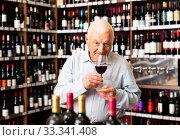 Older man customer holding glass of wine before buy it in a wine house. Стоковое фото, фотограф Яков Филимонов / Фотобанк Лори
