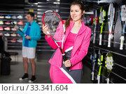 Sporty couple is demonstraiting new rocket and sportwear for tennis. Стоковое фото, фотограф Яков Филимонов / Фотобанк Лори