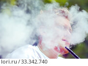 A young man relaxes in nature and releases smoke while smoking a hookah. Стоковое фото, фотограф Акиньшин Владимир / Фотобанк Лори