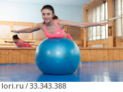 Woman does exercises on fitball in gym with fitness equipment. Стоковое фото, фотограф Яков Филимонов / Фотобанк Лори