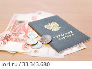 Трудовая книжка и российские деньги на столе. Стоковое фото, фотограф Наталья Осипова / Фотобанк Лори