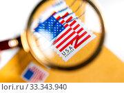 Конверт отправленный из США с маркой с изображением американского флага под увеличительным стеклом. Стоковое фото, фотограф Николай Винокуров / Фотобанк Лори