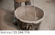 Купить «Concrete industry - worker mixing dry cement with pieces of glass in the bucket», видеоролик № 33344116, снято 5 июня 2020 г. (c) Константин Шишкин / Фотобанк Лори