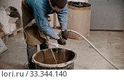Купить «Concrete industry - young man worker adding water in the bucket full of cement», видеоролик № 33344140, снято 5 июня 2020 г. (c) Константин Шишкин / Фотобанк Лори