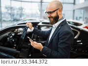Man talks by mobile phone in car dealership. Стоковое фото, фотограф Tryapitsyn Sergiy / Фотобанк Лори