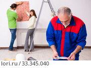 Купить «Young couple and old contractor in home renovation concept», фото № 33345040, снято 2 сентября 2019 г. (c) Elnur / Фотобанк Лори