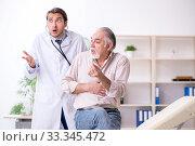Купить «Young male doctor and old patient in antismoking concept», фото № 33345472, снято 9 сентября 2019 г. (c) Elnur / Фотобанк Лори