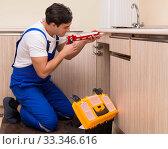 Купить «Young repairman working at the kitchen», фото № 33346616, снято 1 ноября 2016 г. (c) Elnur / Фотобанк Лори