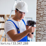 Купить «Repairman working with drilling drill perforator», фото № 33347288, снято 9 декабря 2016 г. (c) Elnur / Фотобанк Лори