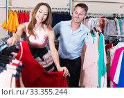 Boyfriend helps his girl to choose a garment. Стоковое фото, фотограф Яков Филимонов / Фотобанк Лори