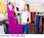 Купить «Young smiling girl trying on new gown», фото № 33355252, снято 11 апреля 2017 г. (c) Яков Филимонов / Фотобанк Лори