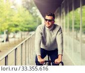 Купить «young man in shades riding bicycle on city street», фото № 33355616, снято 21 августа 2016 г. (c) Syda Productions / Фотобанк Лори