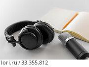 Купить «headphones, microphone and notebook with pencil», фото № 33355812, снято 17 мая 2019 г. (c) Syda Productions / Фотобанк Лори