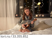 Купить «happy young woman playing guitar in bed at home», фото № 33355852, снято 19 января 2020 г. (c) Syda Productions / Фотобанк Лори