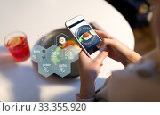 Купить «hands with phone and food nutritional value chart», фото № 33355920, снято 16 января 2017 г. (c) Syda Productions / Фотобанк Лори