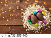 Купить «chocolate eggs and candies in straw nest», фото № 33355940, снято 22 марта 2018 г. (c) Syda Productions / Фотобанк Лори