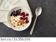 Купить «porridge breakfast with berries, almonds and spoon», фото № 33356016, снято 1 ноября 2018 г. (c) Syda Productions / Фотобанк Лори