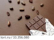 Купить «dark chocolate bar in foil wrapper and cocoa beans», фото № 33356080, снято 1 февраля 2019 г. (c) Syda Productions / Фотобанк Лори