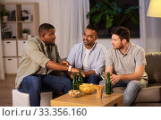 Купить «male friends with smart watch and beer at home», фото № 33356160, снято 28 декабря 2019 г. (c) Syda Productions / Фотобанк Лори