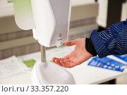 Купить «A man is using a disinfection dispenser in public area», фото № 33357220, снято 7 марта 2020 г. (c) Юлия Кузнецова / Фотобанк Лори