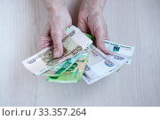 Купить «Old women's hands hold Russian money on the table. The concept of pensions», фото № 33357264, снято 28 февраля 2020 г. (c) Катерина Белякина / Фотобанк Лори