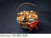 Купить «Wicker basket full of dried fruits and exotic nuts on a dark blue background», фото № 33361524, снято 24 ноября 2019 г. (c) Олег Белов / Фотобанк Лори