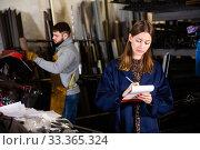 Купить «Young female standing with notepad in production workshop», фото № 33365324, снято 27 мая 2020 г. (c) Яков Филимонов / Фотобанк Лори