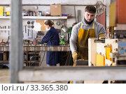 Купить «Man worker during work in workshop, woman on background», фото № 33365380, снято 4 февраля 2020 г. (c) Яков Филимонов / Фотобанк Лори