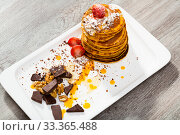 Купить «Pancakes served with fruit, honey, chocolate and whipped cream», фото № 33365488, снято 5 апреля 2020 г. (c) Яков Филимонов / Фотобанк Лори