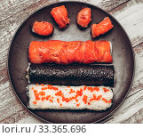 Купить «Various kinds of sushi served on dark plate macro», фото № 33365696, снято 11 марта 2020 г. (c) katalinks / Фотобанк Лори