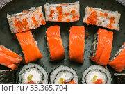 Купить «Various kinds of sushi served on dark plate macro», фото № 33365704, снято 11 марта 2020 г. (c) katalinks / Фотобанк Лори