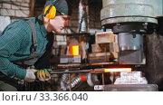 Купить «Blacksmith working - putting a longer hot piece of metal under the pressure of industrial forging machine», видеоролик № 33366040, снято 6 июня 2020 г. (c) Константин Шишкин / Фотобанк Лори