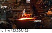 Купить «Blacksmith working - man heating up the longer piece of metal in the furnace and hitting it with a hammer», видеоролик № 33366132, снято 5 июня 2020 г. (c) Константин Шишкин / Фотобанк Лори