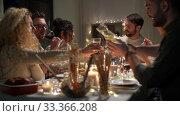 Купить «happy friends having christmas dinner at home», видеоролик № 33366208, снято 9 февраля 2020 г. (c) Syda Productions / Фотобанк Лори