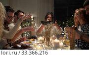 Купить «happy friends having christmas dinner at home», видеоролик № 33366216, снято 9 февраля 2020 г. (c) Syda Productions / Фотобанк Лори