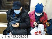 Пассажиры в московском метро в медицинской маске (2020 год). Редакционное фото, фотограф Victoria Demidova / Фотобанк Лори