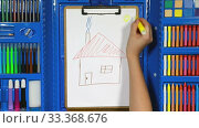 Купить «The girl's hand draws a child's drawing with a house on white paper using various markers from the drawing kit. The concept of a happy childhood.», видеоролик № 33368676, снято 12 марта 2020 г. (c) Алексей Кузнецов / Фотобанк Лори