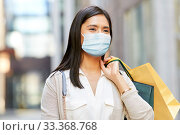 Купить «asian woman in protective mask with shopping bags», фото № 33368768, снято 13 июля 2019 г. (c) Syda Productions / Фотобанк Лори