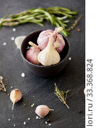 Купить «garlic in bowl and rosemary on stone surface», фото № 33368824, снято 6 сентября 2018 г. (c) Syda Productions / Фотобанк Лори
