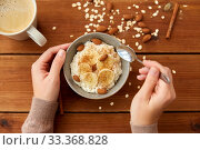 hands with oatmeal breakfast and cup of coffee. Стоковое фото, фотограф Syda Productions / Фотобанк Лори