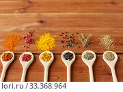 Купить «spoons with different spices on wooden table», фото № 33368964, снято 6 сентября 2018 г. (c) Syda Productions / Фотобанк Лори